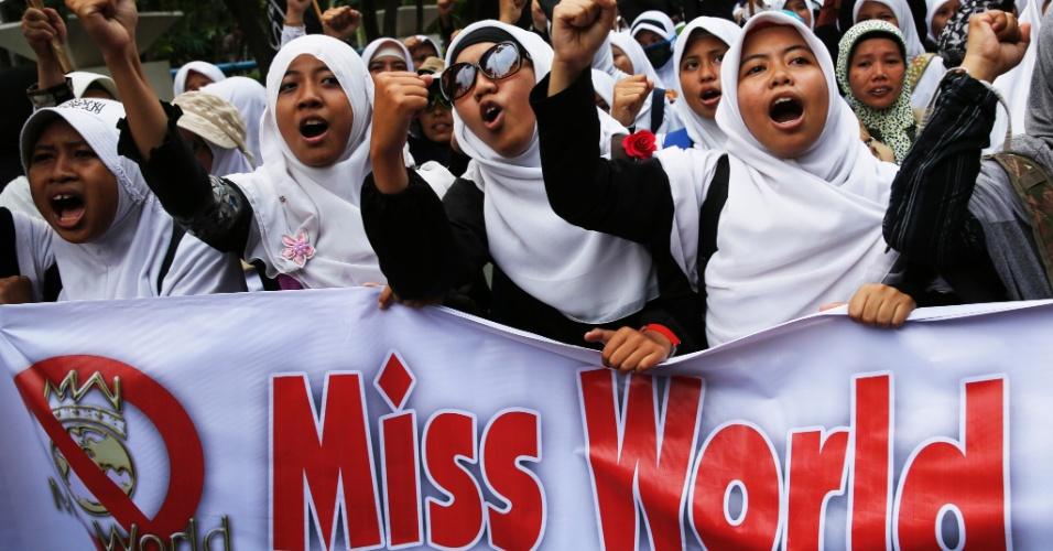 5.set.2013 - Mulheres muçulmanas entoam gritos durante protesto pedindo o cancelamento da realização do concurso de Miss Mundo 2013 na Indonésia. O cartaz --que está cortado-- tem os dizeres: