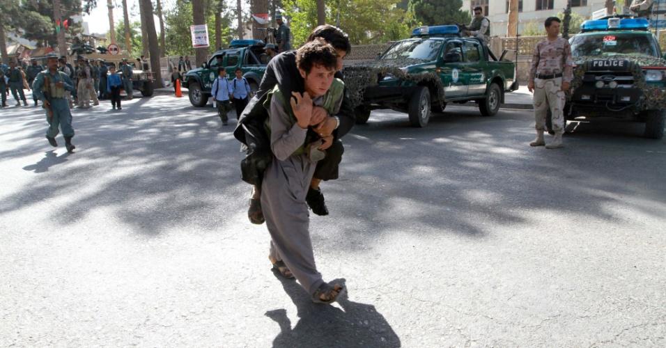 7.set.2013 - Afegão socorre ferido durante protesto contra o consulado indiano em Herat (Afeganistão)