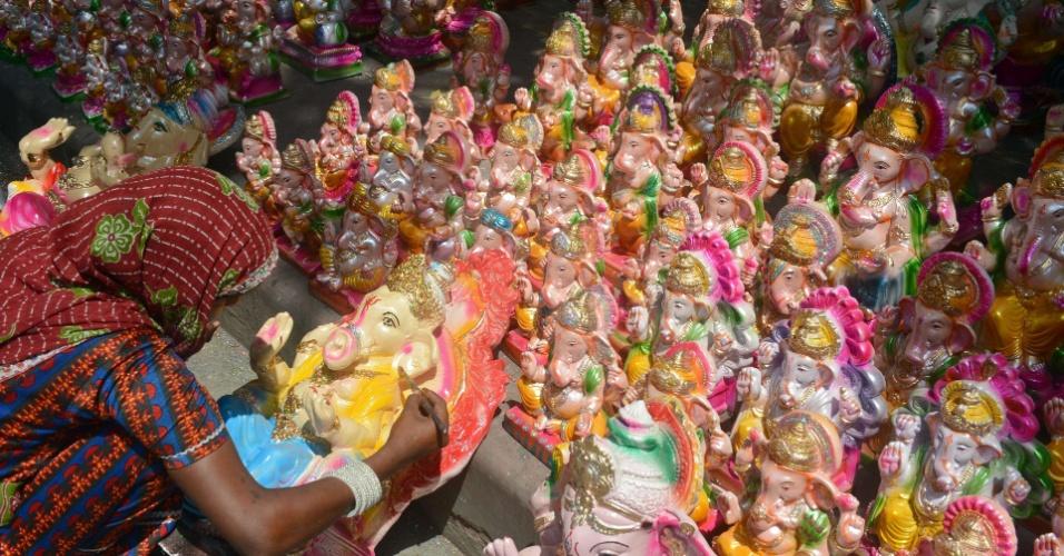 7.set.2013 - Artesão indiano decora ídolo em mercado de beira da estrada próximo do festival Ganesh Chaturthi, em Nova Délhi, na Índia, neste sábado (7). O festival hindu, que começa no dia 9 de setembro e termina no dia 19, celebra o renascimento de Ganesha