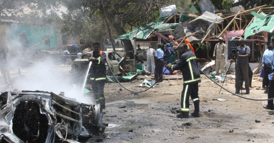7.set.2013 - Bombeiros apagam fogo de veículo após duas explosões em Mogadíscio, capital da Somália, neste sábado (7). Segundo a polícia, pelo menos nove pessoas morreram após duas explosões que destruíram um estacionamento ocupado perto do Teatro Nacional