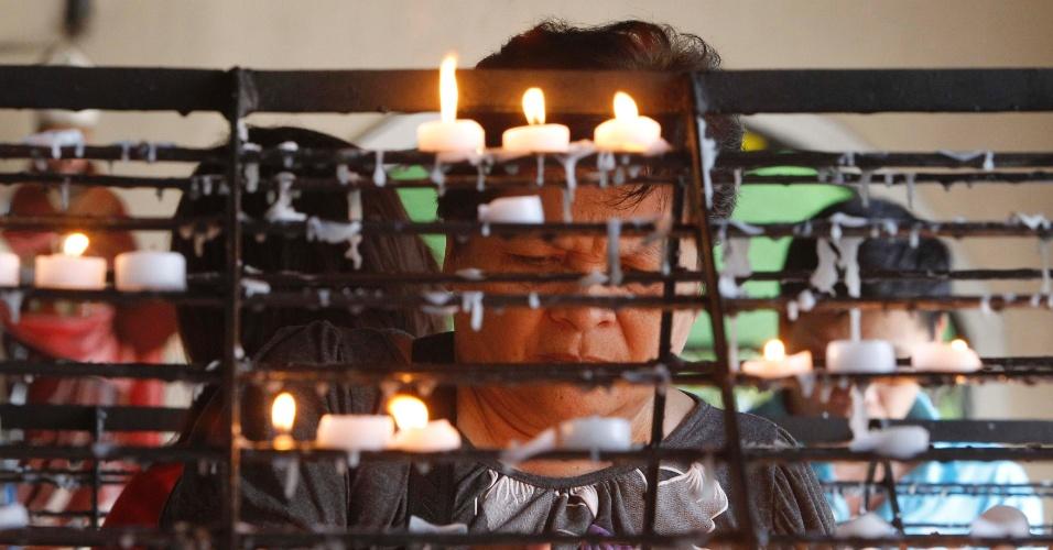 7.set,2013 - Devota católica acende vela antes de assistir à missa em homenagem à Maria do Perpétuo Socorro, em igreja de Paranaque, na região de Manila (Filipinas)