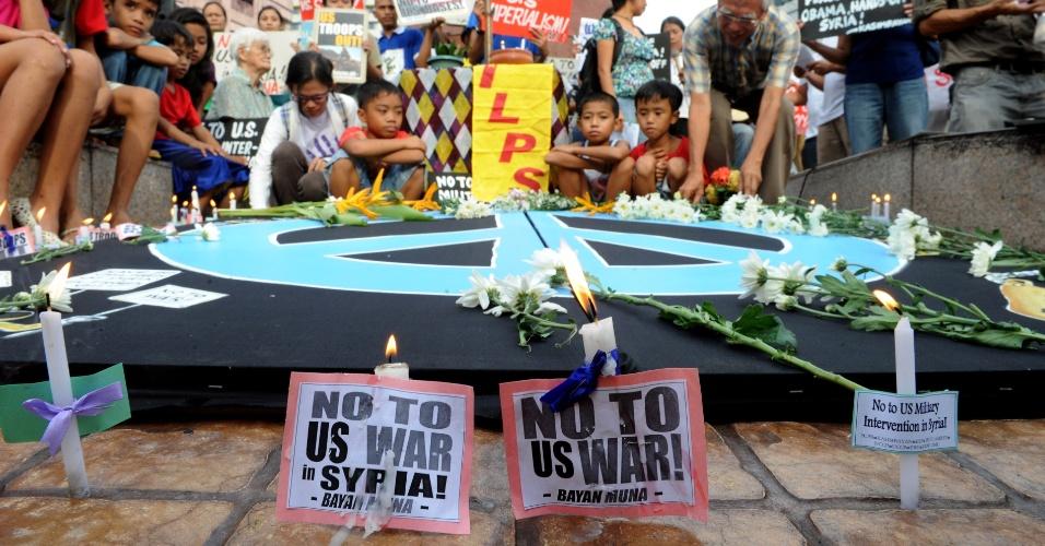 7.set.2013 - Filipinos seguram cartazes antiamericanos e acendem velas durante uma vigília pela Síria, em Manila capital do país. Os manifestantes são contra uma intervenção militar americana na Síria