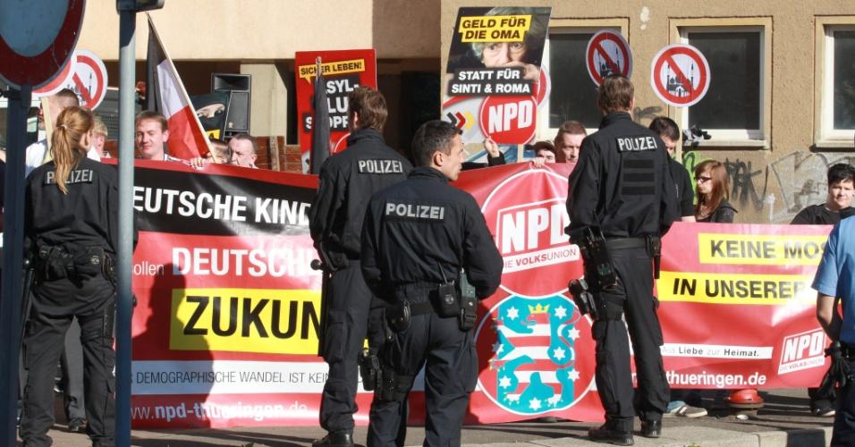 7.set.2013 - Policiais montam guarda durante reunião de ativistas de extrema-direita do Partido Nacional Democrático da Alemanha (NPD) próximo da casa de requerentes de asilo em Gera, na Alemanha, neste sábado (7). O partido protesta contra os requerentes de asilo e migrantes