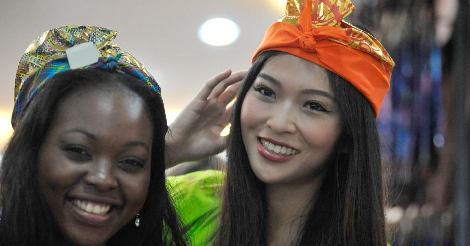 6.set.2013 - Candidatas Mamahlape Caroline Matsoso (esq.), do Lesoto, e Cinzia Chang, de taiwan, posam para foto durante passeio ao templo Tanah Lot, em Bali