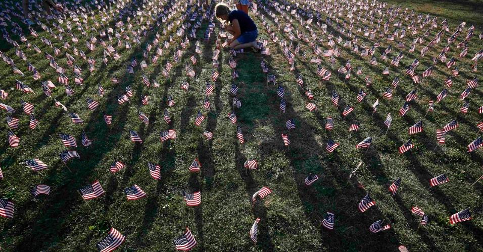 11.set.2013 - Garota coloca uma das 3.000 bandeiras dos Estados Unidos dispostas em gramado em memória das vítimas do atentado terrorista de 11 de setembro de 2001, em um parque em Winnetka, no Estado de Illinois, nos Estados Unidos