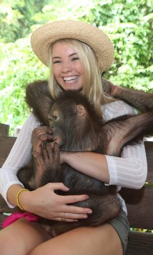 12.set. 2013 - Miss Bermudas Katherine Arnfield abraça um orangotango durante safári em Bali, Indonésia