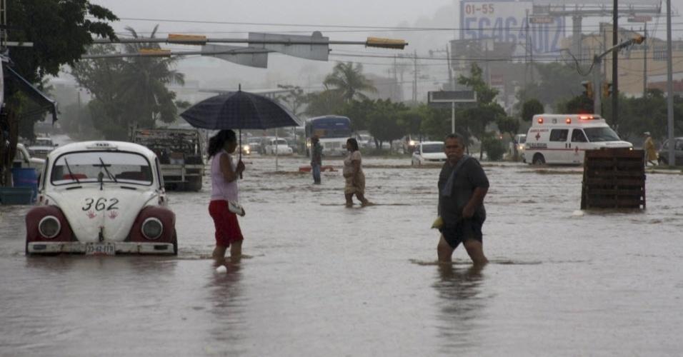 16.set.13 - Mexicanos caminham em via alagada em Acapulco no último domingo (15). O furacão Ingrid e a tempestade tropical Manuel trouxeram fortes chuvas ao Golfo do México e aos povoados da costa do Pacífico, causando enchentes e matando ao menos 21 pessoas, segundo as autoridades locais