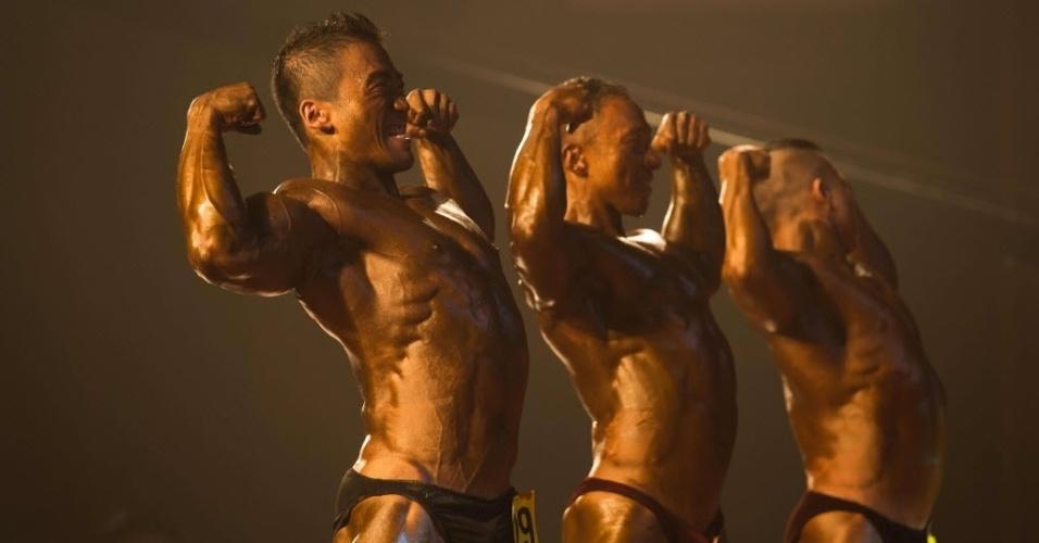 16.set.2013 - Em uma foto tirada no domingo (15), fisiculturistas amadores da China exibem os músculos no palco durante uma competição de fisiculturismo em Zhengzhou, província de Henan. Mais de 20 atletas participaram do Grand Prix Musculação na cidade chinesa para um prêmio equivalente a US$ 13 mil