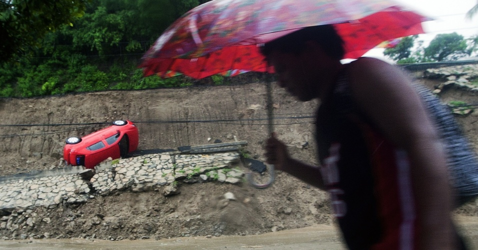 16.set.2013 - Homem caminha por rua de Acapulco, no México, após a passagem do Furacão Ingrid, nesta segunda-feira (16), com carro arrastado pela força das enchentes ao fundo. Em diferentes áreas de Acapulco, a água alcançou um metro de altura, carregando carros e forçando o fechamento da estrada que leva ao aeroporto internacional