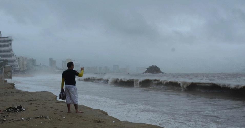 16.set.2013 - Homem fotografa ondas em uma praia afetada pelo furacão Ingrid e a tempestade tropical Manuel, em Acapulco, no México. Pelo menos trinta pessoas morreram desde o último fim de semana e há pelo menos 200 mil pessoas afetadas pelo impacto simultâneo de dois ciclones tropicais, um fenômeno raro que não se presenciava havia meio século