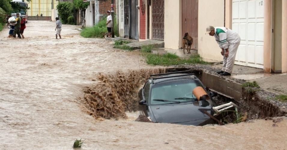 17.set.2013 - Homem observa carro preso em buraco em rua inundada da cidade de Chailpancingo, no México, nesta terça-feira (17). Pelo menos 48 pessoas morreram e mais 230.000 estão desabrigadas por causa da passagem pelo México das tempestades Ingrid e Manuel
