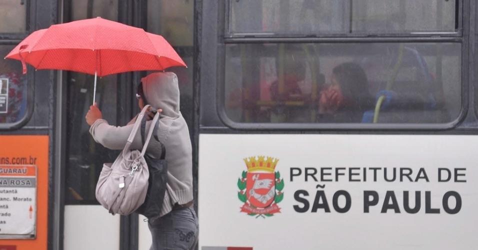 17.set.2013 - Mulher segurando um guarda-chuva circula pela avenida Brigadeiro Faria Lima, em São Paulo (SP), nesta terça-feira (17) chuvosa. No segundo dia de funcionamento do novo sistema de trânsito que prevê mão única de direção para veículos na região central, a rótula central, usuários do transporte público relatam rapidez, apesar da lotação