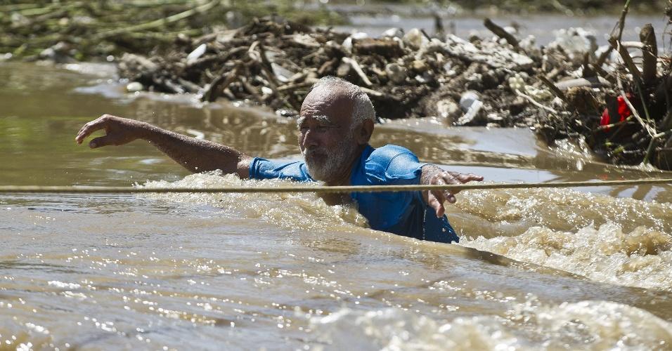 18.set.2013 - Idoso tenta atravessar rua completamente inundada em Acapulco, no Estado de Guerrero, no México, nesta quarta-feira (18). Cerca de 40 mil turistas que estavam na região ficaram a espera de resgate, após a passagem da tempestade tropical Manuel