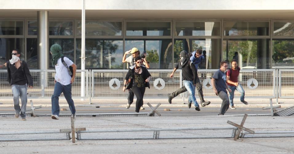 18.set.2013 - Manifestantes derrubam grade em frente ao Palácio do Planalto, em Brasília, nesta quarta-feira (18) em protesto contra o voto do ministro do STF Celso de Mello que aceitou os embargos infringentes dos réus do mensalão, reabrindo o julgamento para 12 dos condenados