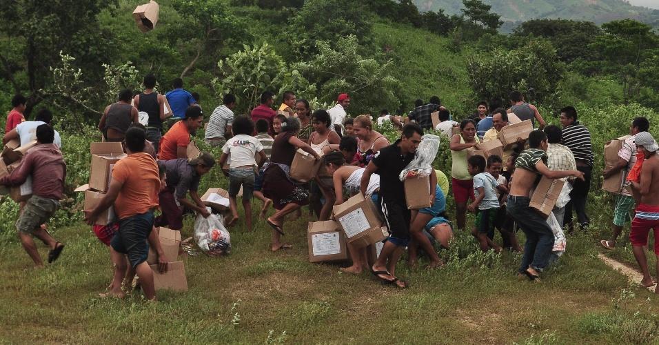 18.set.2013 - Pessoas pegam caixas com comida lançadas do ar por um helicóptero das Forças Armadas mexicana em Acapulco, no Estado de Guerreiro, no México. O país foi afetado, desde o fim de semana, pela passagem do furacão Ingrid e da tempestade tropical Humberto. São foram contabilizados cercar de 80 mortos e milhares de desabrigados