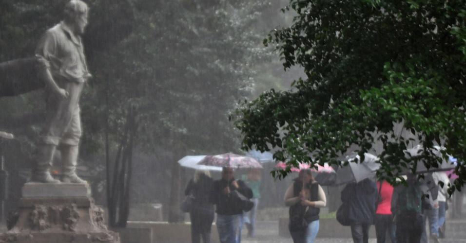 19.set.2013 - Paulistanos se protegem da chuva na avenida Paulista, região central de São Paulo, na manhã desta quinta-feira (19)