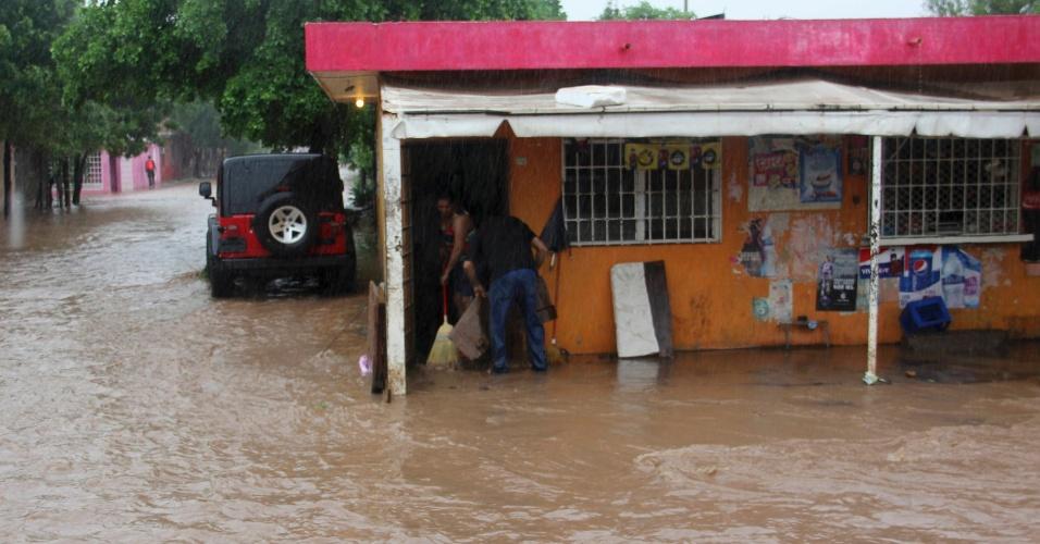 19.set.2013 - Pessoas tentam tirar água de dentro de loja, que fica perto de um rio que transbordou em um bairro de Culiacan, nesta quinta-feira (19). A tempestade tropical Manuel atingiu a costa leste noroeste do México com fortes chuvas