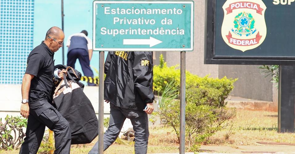 19.set.2013 - Policiais carregam ouro objetos e artigos de luxo, além de dinheiro vivo, apreendidos na Operação Miqueias, para a sede da superintendência da Polícia Federal, em Brasília, nesta quinta-feira (19). Cálculo é de que a quadrilha tenha lavado cerca de R$ 300 milhões