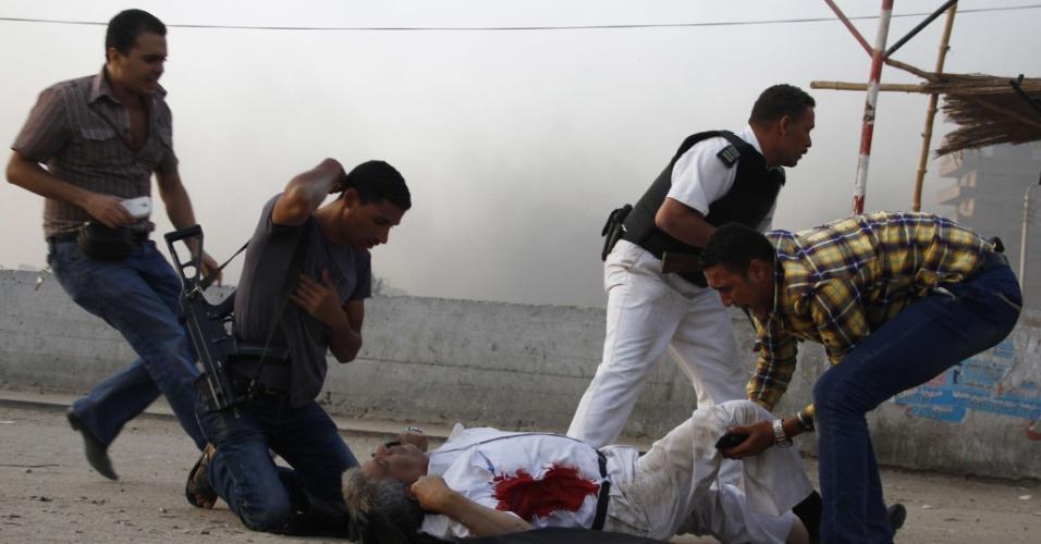 19.set.2013 - Policiais egípcios socorrem chefe de segurança Nabil Farrag, depois de ele ter sido baleado durante uma incursão na aldeia de Kerdassah nos arredores de Cairo, nesta quinta-feira (19). Farrag foi morto quando forças de segurança egípcias invadiram Kerdassah na última ofensiva contra militantes islâmicos, disseram autoridades de segurança
