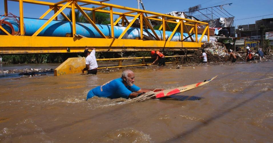 19.set.2013 - Um homem usa uma prancha de surf para atravessar uma rua inundada em Acapulco, México.  Autoridades tentam retirar as pessoas que permanecem isoladas na região por conta dos alagamentos