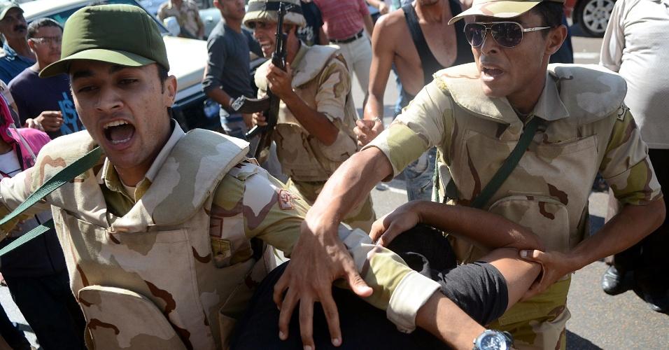 20.set.2013 - Membros das forças de segurança do Egito prendem manifestantes durante protesto em apoio ao presidente egípcio deposto Mohammed Mursi e contra os militares, nesta sexta-feira (20), ao longo da beira-mar da cidade de Alexandria, na costa norte do país. Apoiado pelas autoridades, o Exército prendeu o porta-voz da Irmandade Muçulmana na última terça-feira (17) e congelou os bens de outros islamitas, em um novo golpe para os defensores do presidente deposto