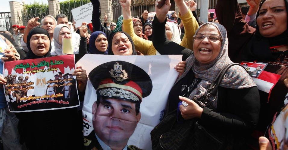 20.set.2013 - Pessoas de luto seguram cartaz com foto do chefe do Exército, general Abdel Fattah al-Sisi, durante o funeral do general Nabil Farag, morto na última terça-feira (17), em Kerdasa. Farrag morreu depois de militantes não identificados abrirem fogo contra forças de segurança que estavam na cidade de Kerdasa para expulsar supostos islamitas, os quais lutavam para tomar o controle do local, próximo às pirâmides de Gizé