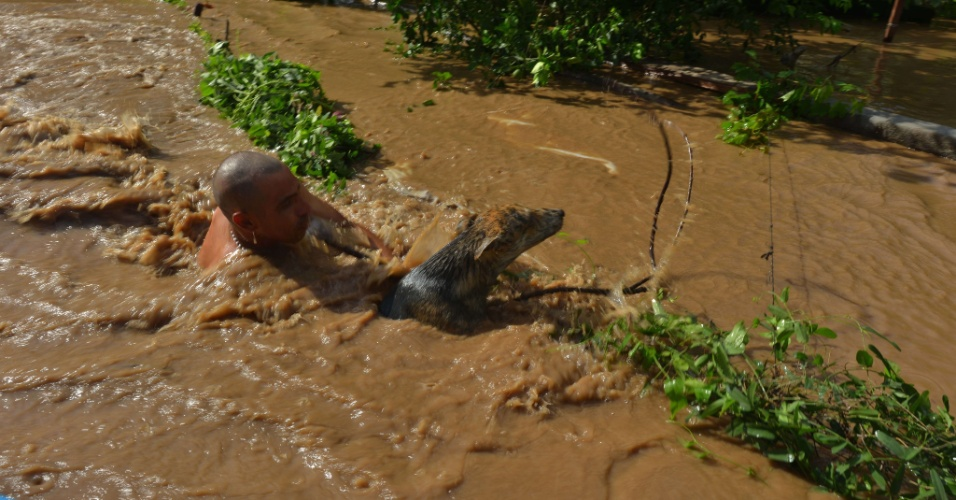 """21.set.2013 - Mexicano resgata cão que estava sendo arrastado pela correnteza de águas de rua inundada durante passagem do furacão """"Manuel"""", em Navolato, no Estado de Sinaloa (México)"""