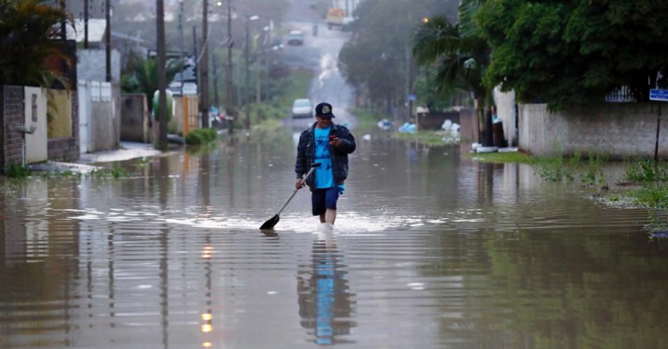 21.set.2013 - Morador passa por área alagada na cidade de Rio do Sul (SC). O volume de chuvas ultrapassaram o previsto para todo o mês de setembro em algumas regiões do Estado. Em Rio do Sul, choveu 70 mm até sexta-feira (20). Famílias estão sendo retiradas de suas casas como prevenção aos alagamentos
