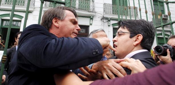 O deputado Jair Bolsonaro (PP-RJ) (esquerda) e o senador Randolfe Rodrigues (PSOL-AP) discutem enquanto membros da Comissão da Verdade entravam no 1º Batalhão da Polícia do Exército