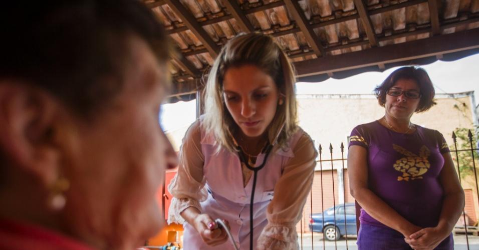 24.set.2013 - A médica cubana Tania Sosa, 45, (de roupa roxa) visita a casa da paciente em SP acompanhada por uma enfermeira. Já instalados nos municípios onde irão atuar nos próximos três anos mas ainda sem o registro de trabalho, médicos cubanos passaram a segunda-feira (23) dando entrevistas, visitando postos de saúde, acertando detalhes burocráticos com prefeituras e até recebendo presentes