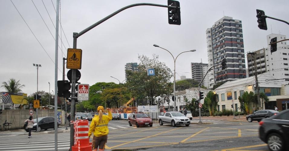 24.set.2013 - Guarda da CET (Companhia de Engenharia de Tráfego) orienta o trânsito na manhã desta terça-feira (24) por causa de semáforo apagado após chuvas, no cruzamento das avenidas Ibirapuera e Indianópolis, na zona sul de São Paulo; trânsito; indoor; normal