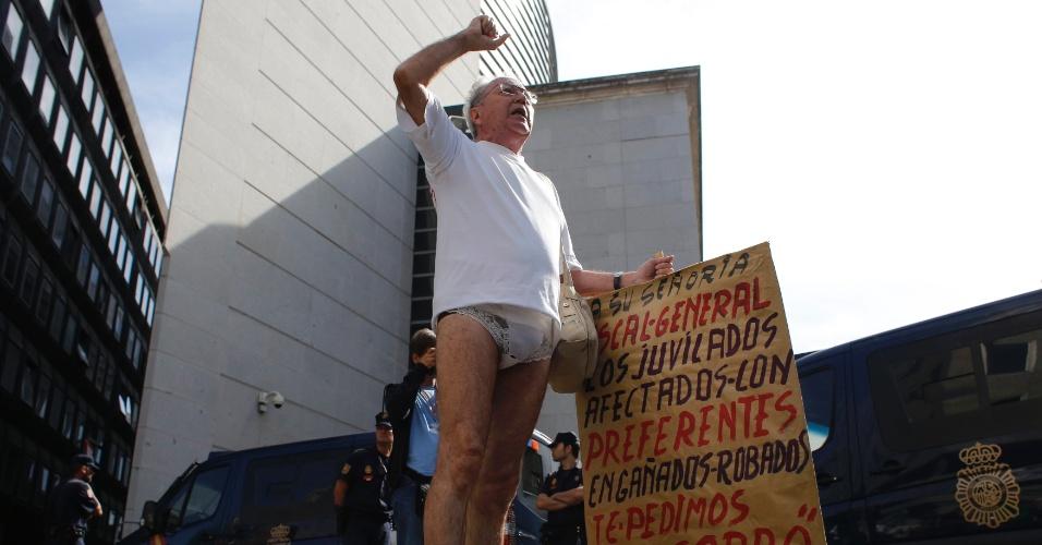 """26.set.2013 - Homem afetado pela queda nos preços das ações preferenciais do banco credor espanhol Bankia protesta usando uma calcinha do lado de fora do Parlamento em Madri, na Espanha. No cartaz, ele utiliza uma expressão espanhola e diz que os aposentados foram enganados e deixados """"só de calcinha"""""""