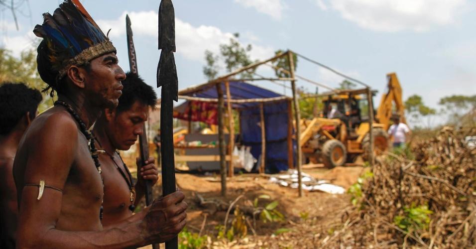 26.set.2013 - Índios aguardam enquanto trator destrói abrigos por ordem judicial expedida em disputa por propriedade de terras em Iranduba, próximo a Manaus (AM)