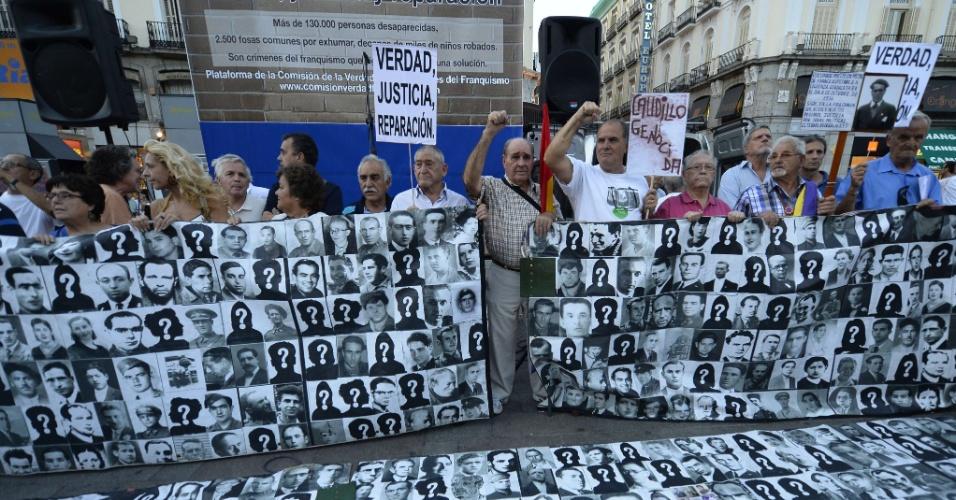 26.set.2013 - Manifestantes seguram faixas com retratos de pessoas que foram mortas ou torturadas durante a ditadura de Francisco Franco em frente à antiga sede da Segurança Nacional, em Madri