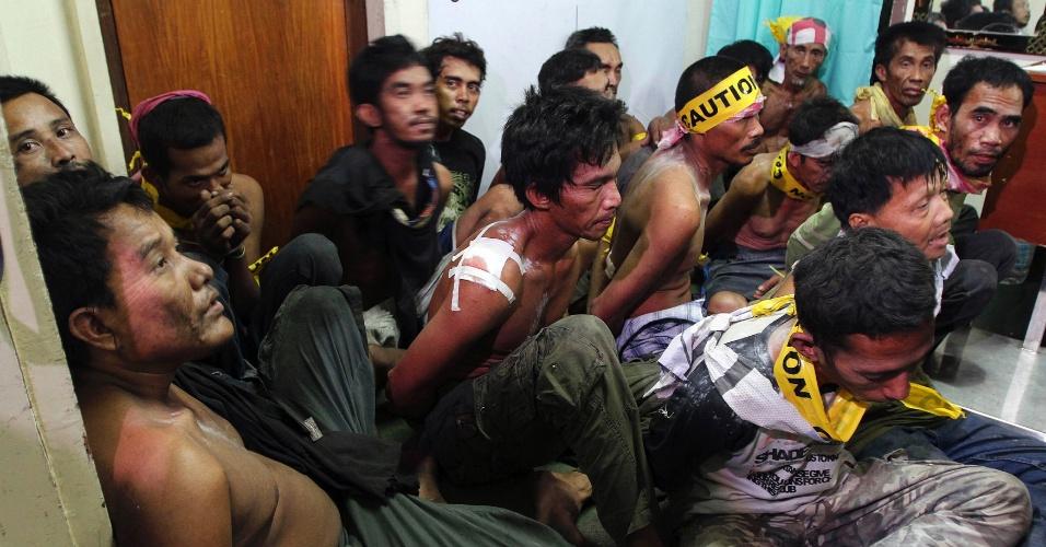 26.set.2013 - Membros de grupo rebelde muçulmano são presos por soldados do governo e aguardam vistoria de impressão digital em delegacia na cidade de Zamboanga, no sul das Filipinas