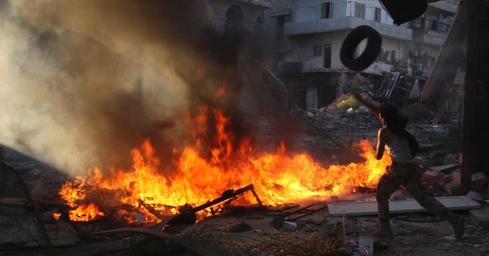 26.set.2013 - Militante do Exército Livre da Síria joga pneu em barricada em chamas em Aleppo, durante confronto contra forças leais ao regime do ditador Bashar al-Assad