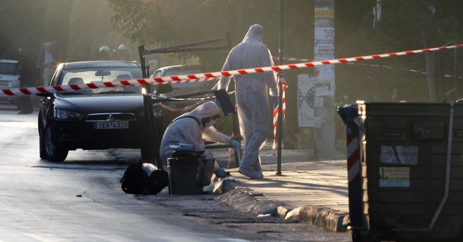 26.set.2013 - Policiais investigam nesta quinta-feira (26) escritório onde bomba explodiu, em bairro rico de Atenas (Grécia). A explosão danificou a entrada do prédio e destruiu janelas, mas não feriu gravemente ninguém, de acordo com a polícia
