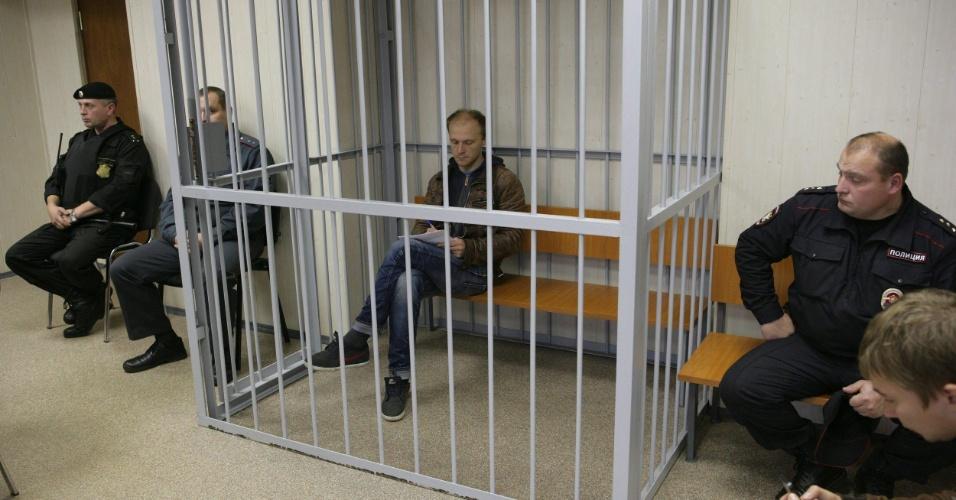 26.set.2013 - Policiais montam guarda perto de jaula com o fotógrafo do Greenpeace Denis Sinyakov, no tribunal de Murmansk, na Rússia. O tribunal prolongou por dois meses a detenção de Sinyakov, um dos 30 ativistas do Greenpeace presos no protesto contra uma plataforma petrolífera da gigante russa Gazprom no Ártico, informou a organização ecologista