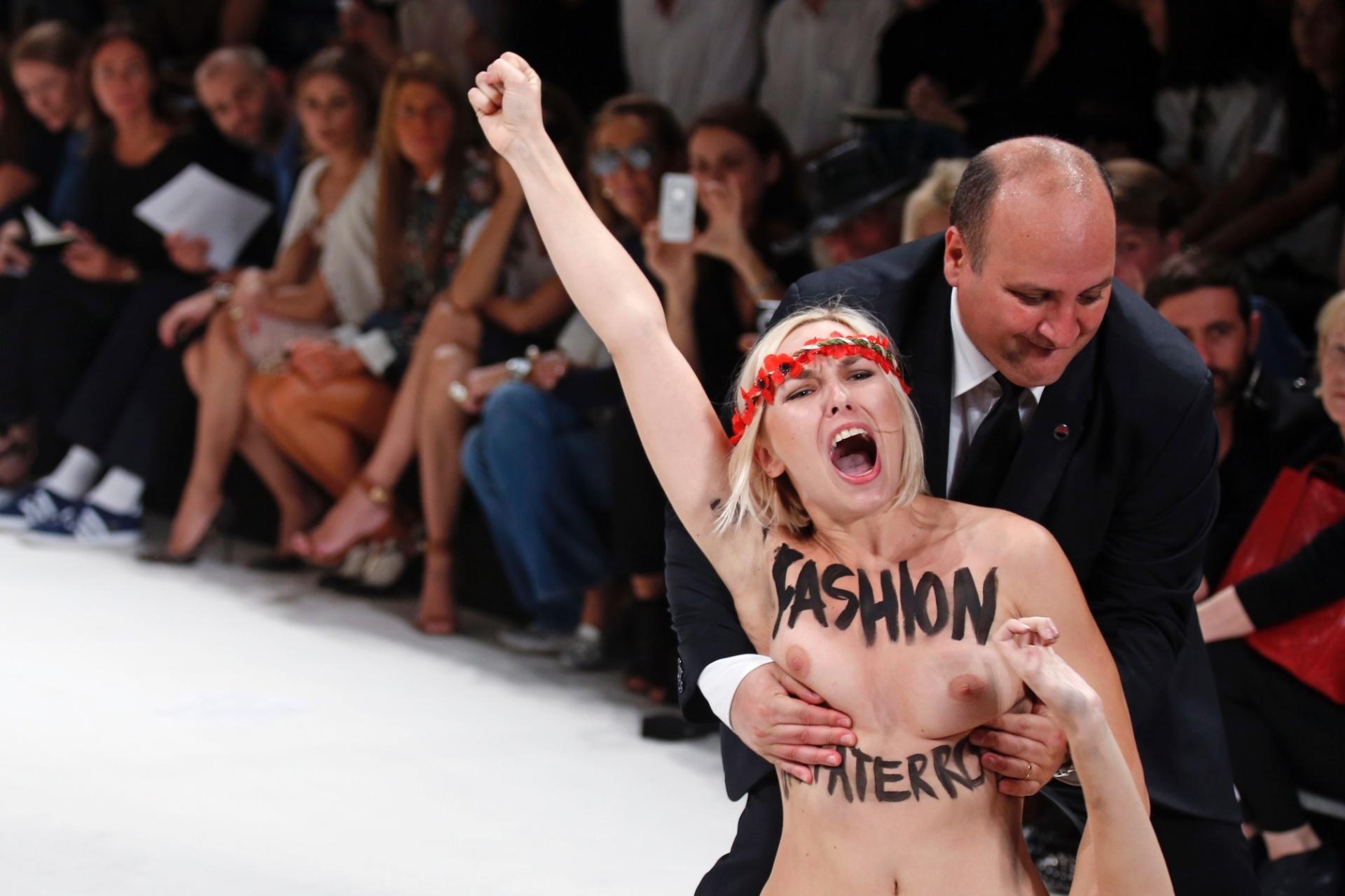 26.set.2013 - Segurança retira ativista do grupo feminista Femen que invadiu passarela durante desfile Primavera/Verão 2014 da marca Nina Ricci, em Paris, na França. Em seu corpo está escrito com tinta: