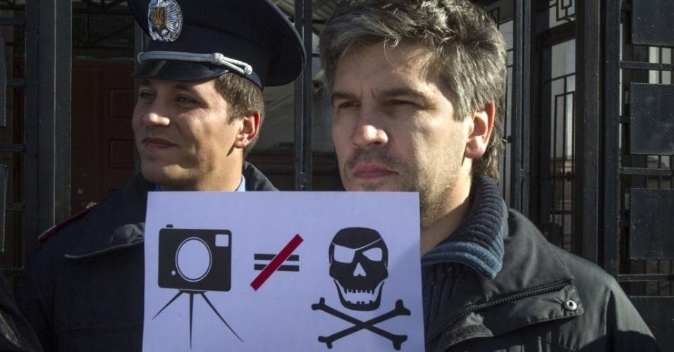 27.set.2013 - Fotojornalista protesta em frente à Embaixada da Rússia em Kiev, na Ucrânia, contra a prisão preventiva de Denis Sinyakov. O fotógrafo russo, que acompanhava a ação do Greenpeace contra a exploração de petróleo no Ártico, está sob custódia das autoridades russas por até dois meses sob a acusação de pirataria