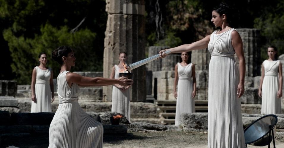 28.set.2013 - A atriz grega Ino Menegaki (d) passa a chama olímpica neste sábado (28) para um recipiente que será levado até Sochi, na Rússia, palco da Olimpíada de Inverno de 2014. A cerimônia acontece no templo da cidade grega de Olímpia, onde os jogos surgiram em 776 a.C.