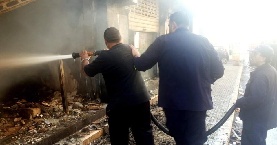 28.set.2013 - Bombeiros tentam apagar incêndio em um centro comercial no Líbano neste sábado (28). As lojas pegaram fogo durante um tiroteio entre membros do Hezbollah e dos sunitas da al-Shiah. De acordo com a imprensa local, ao menos cinco pessoas teriam se ferido no confronto