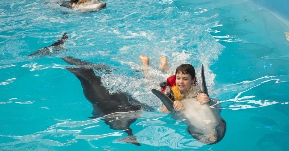 28.set.2013 - Crianças ucranianas 'surfam' com golfinhos em parque aquático de capital do país, Kiev, neste sábado (28). O centro promove um programa de terapia para mulheres grávidas, crianças e portadores de deficiências físicas que envolve brincadeiras e aulas de natação com os animais