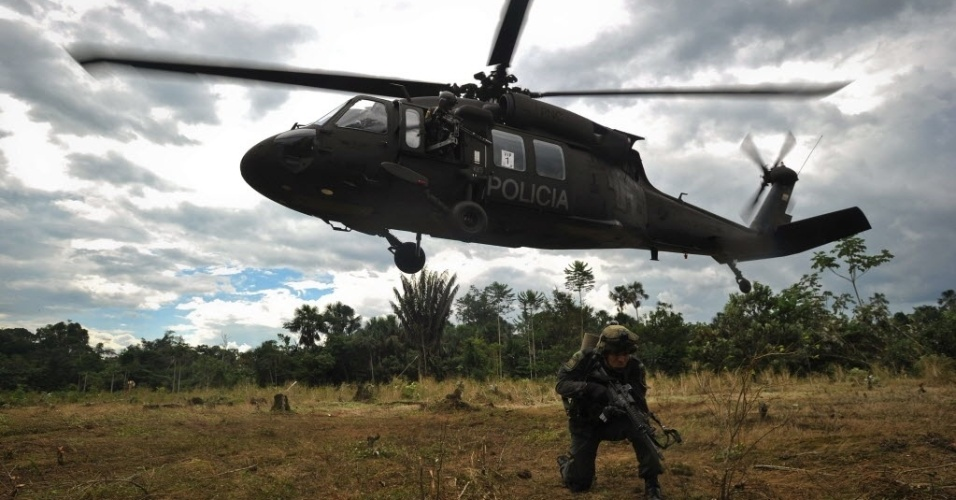28.set.2013 - Helicóptero da polícia colombiana chega a terreno de plantação de coca na área rural de Puerto Asis, fronteira com o Equador. Na última sexta-feira (27), foi divulgado que o líder das Farc, Timoleón Jiménez, teria ameaçado divulgar um relatório que revelaria aspectos desconhecidos do processo de paz