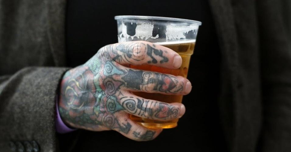 28.set.2013 - Homem com tatuagens na mão segura copo com bebida durante 9ª Convenção Internacional de Tatuagem em Londres. O evento reúne cerca de 300 artistas