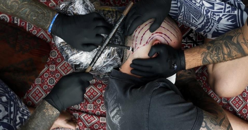 28.set.2013 - Homem é tatuado pelo artista Brent McCown (à esquerda) durante 9ª Convenção Internacional de Tatuagem em Londres. O evento reúne cerca de 300 artistas