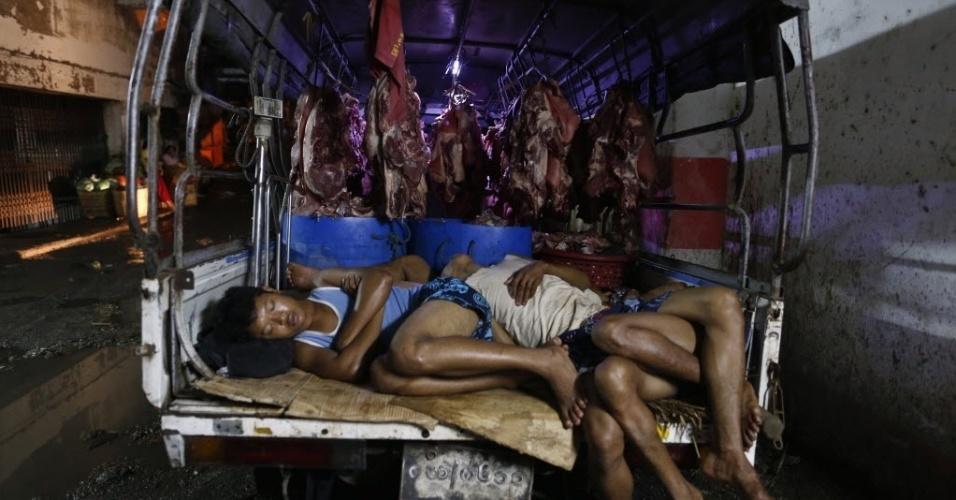 28.set.2013 - Homens dormem dentro de caminhão cheio de carnes enquanto esperam a abertura do Thanzay em Yangon (Mianmar), neste domingo (29). Thanzay é o maior mercado de carnes da capital