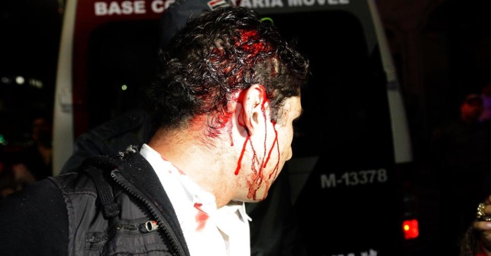 28.set.2013 - Manifestante ferido é detido na noite desta sexta-feira (27), durante um protesto contra a aceitação, por parte do STF (Supremo Tribunal Federal), dos embargos infringentes de condenados no julgamento do mensalão