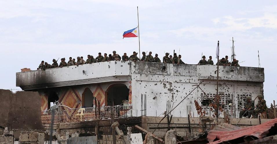 28.set.2013 - Soldados filipinos montam guarda em edificação destruída após semanas de confrontos com insurgentes muçulmanos em Zamboanga (sul das Filipinas)
