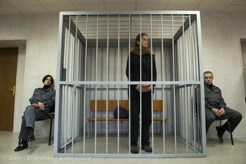 2.out.2013 - Cercada por guardas e dentro de uma jaula, a brasileira Ana Paula Maciel escuta instrução da Corte de Murmansk, no noroeste da Rússia, durante audiência que decretou sua prisão preventiva. A promotoria russa apresentou nesta quarta-feira uma acusação de pirataria contra 14 ativistas do Greenpeace, entre eles a brasileira de 31 anos